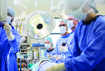 Doctors performing surgery in operating theater, looking at monitor